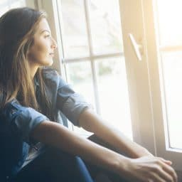 Smiling young woman sitting and looking through the window. With long hair, wears denim shirt. Hands on legs.