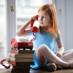 Young girl sitting on a table talking on the phone