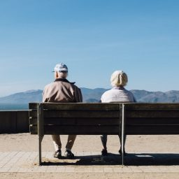 Older couple sitting on a bench together.
