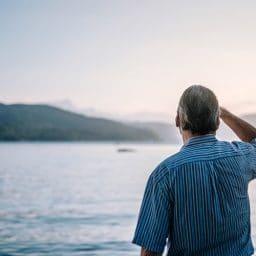 Man stares out at a lake.