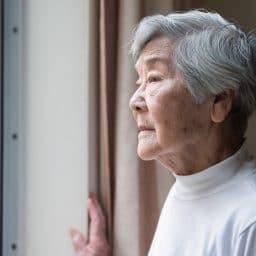 Older woman looking outside a window.